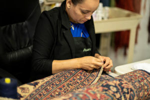 A female employee at S&S Rug Cleaners provides a rug repair in Atlanta