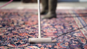 Employee at S&S Rugs, an Atlanta rug cleaning service company, air dusting an oriental rug